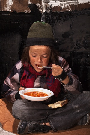Poor beggar child eating charity food on the street sitting on cardboard plank