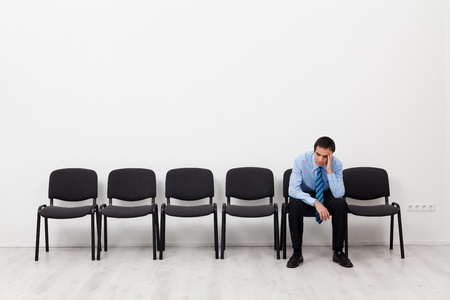 prompting: Desperate businessman or employee sitting alone prompting his head
