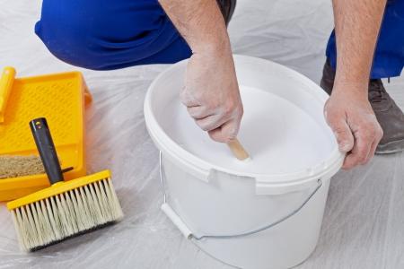 stirring: Worker hands stirring white paint before applying it - closeup