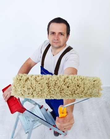Worker on ladder holding paint roller - redecorating concept photo