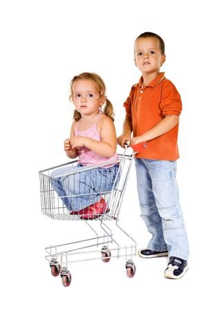 niño empujando: La compra de una pequeña hermana - muchacho empujando el carrito de la compra con una chica en el interior Foto de archivo