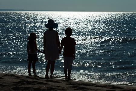 the farewell: Adiós al mar - la mujer y los niños siluetas contra la superficie del agua brilla