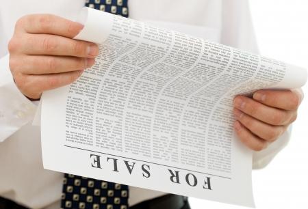 classifieds: Businessman reading sales ads - closeup on hands and lorem ipsum paper