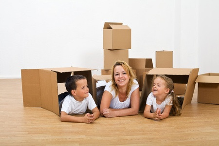 play room: Happy woman and kids relaxing in their new home - moving in with carboard boxes Stock Photo