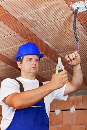 Electrician working with the ceiling wiring in a new building photo