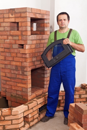 Mason building a traditional stove from red clay bricks - holding the door Stock Photo - 22060637