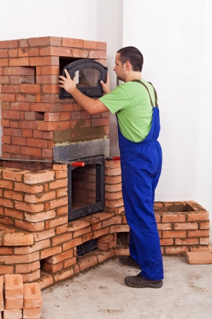 firebox: Worker in uniform building a traditional stove from bricks - fitting the doors