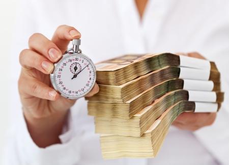 mucho dinero: Limitada oferta concepto de tiempo con la pila de dinero y cron�metro en manos de la mujer - profundidad
