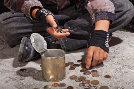 begging: Beggar child counting coins sitting on damaged concrete floor - closeup on hands