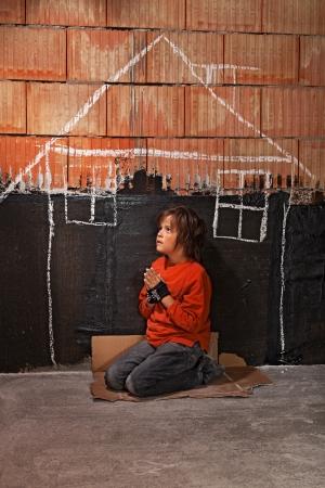 yearning: Poor homeless beggar boy praying for a shelter concept - kneeling on cardboard