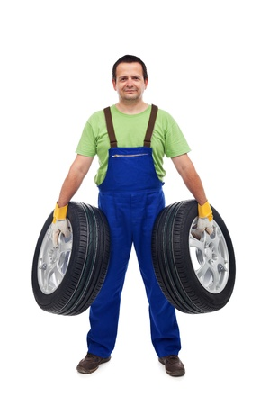 Smiling car mechanic holding two tires - isolated Stock Photo - 22060579