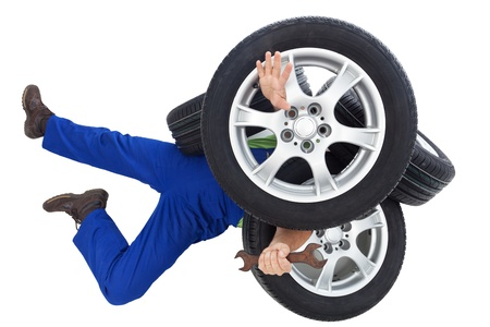 inexperienced: Mechanic covered by car tires - on white background