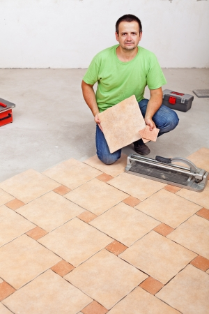 Worker laying floor tiles on concrete surface in a new building photo