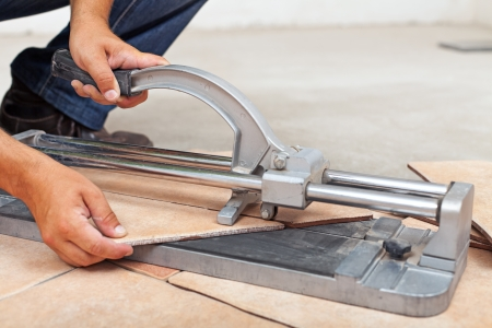 Worker cutting floor tiles with manual cutter - closeup photo