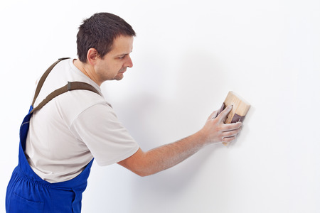 sandpaper: Worker scrubbing the wall with sandpaper - preparing the surface for painting