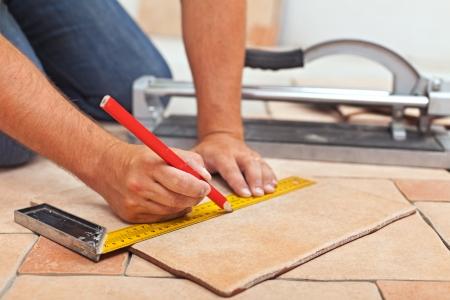 trabajando en casa: Colocaci�n de las baldosas cer�micas - hombre manos de marcado baldosas a cortar, primer Foto de archivo