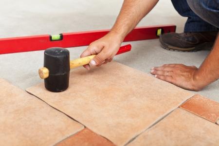 Installing ceramic flooring closeup on man hands fitting a tile Standard-Bild