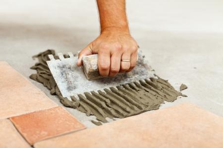 tile adhesive: Laying ceramic floor tiles - man hand spreading adhesive material, closeup Stock Photo