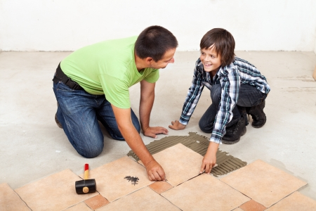 tile adhesive: Smiling father and son laying ceramic floor tiles together Stock Photo