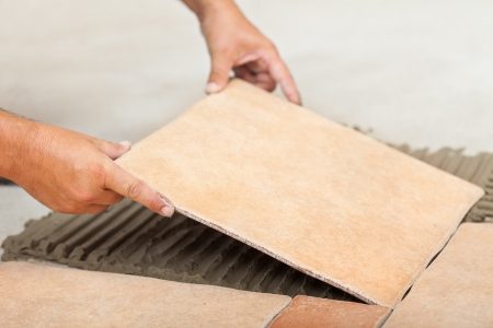 Laying ceramic floor tiles - man hands fitting the next piece, closeup photo