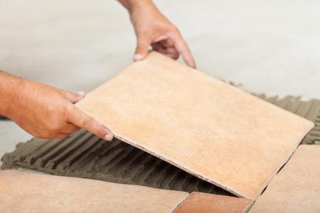 tile adhesive: Laying ceramic floor tiles - man hands fitting the next piece, closeup