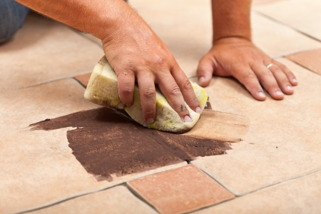 Laying ceramic floor tiles - man hands testing the color of joint on a small area photo