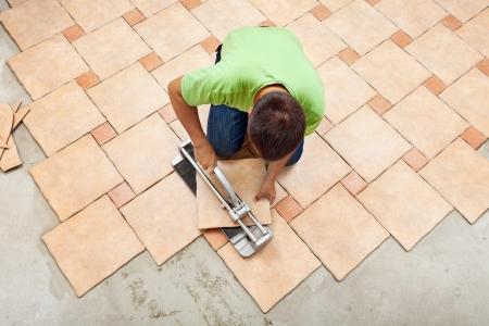 상위 뷰 - 커터 장치와 함께 작동하는 세라믹 바닥 타일을 누워있는 사람