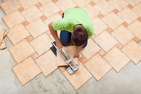 tile flooring: Man laying ceramic floor tiles working with a cutter device - top view