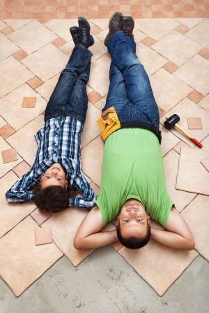 Father and son resting while laying ceramic floor tiles