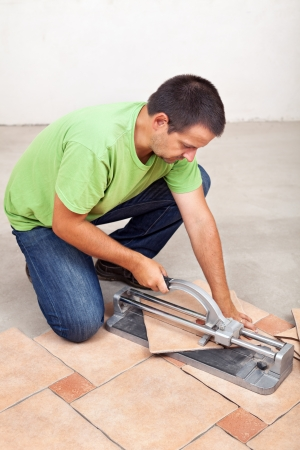 Man Cutting Floor Tiles With Manual Cutter Device Stock Photo