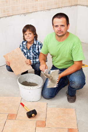 tile adhesive: Father and son laying ceramic floor tiles together in a new home