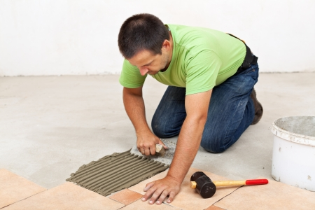 Man laying ceramic floor tiles - spreading the adhesive material Stock Photo - 22247618