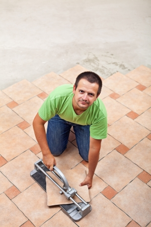 Man laying ceramic floor tiles - top view, copy space Stock Photo - 22247620