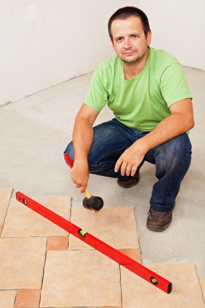 placing: Worker laying ceramic floor tiles crouching and holding a rubber hammer Stock Photo
