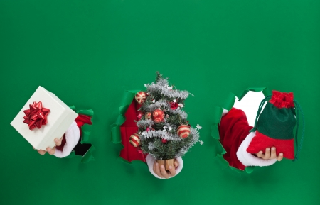 hands holding tree: Christmas symbols bursting through green background - copy space Stock Photo