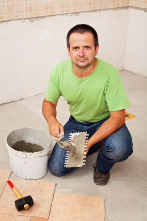 Worker laying ceramic floor tiles on concrete surface - spreading the adhesive material photo