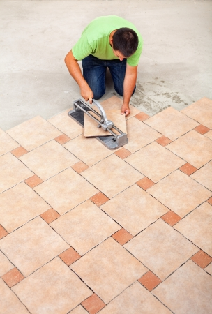 tiler: Man laying ceramic floor tiles - top view with copy space Stock Photo