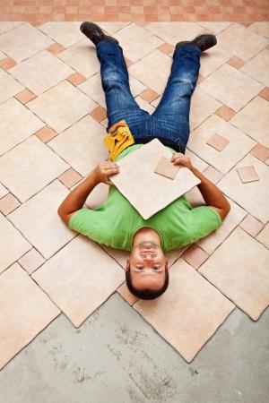 Man resting on ceramic floor tiles - taking a short break photo