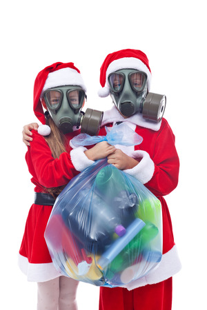 Santa and helper wearing gas masks holding bag of used plastic bottles waste - isolated photo