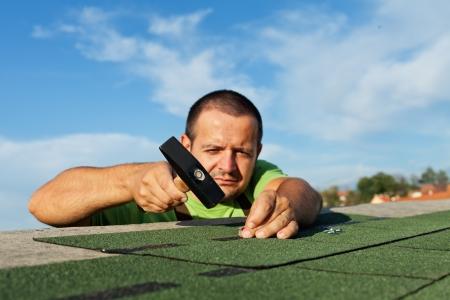 Man installing bitumen roof shingles - using a hammer and nails Standard-Bild