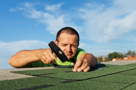 Man installing bitumen roof shingles - using a hammer and nails Zdjęcie Seryjne