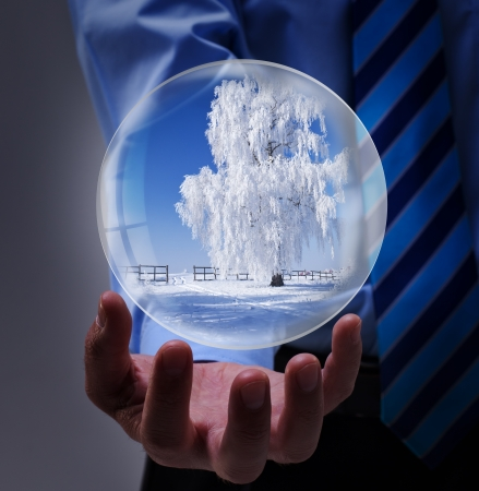 Winter offer or holidays travel incentive in businessman hands inside snow globe photo