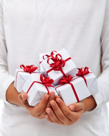 thankfulness: Lots of christmas presents in child hands - thankfulness for abundance concept, with copy space Stock Photo