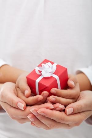 De vreugde van het geven met Kerstmis - kleine gift box aan vrouw en kind handen, close-up