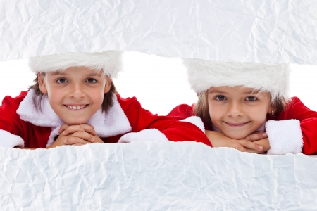 Kids watching the unwrapping christmas present - looking through torn paper strip, copy space photo