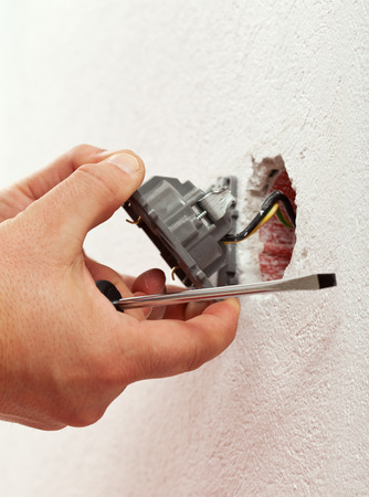 fixture: Electrician mounting electrical wall fixture - closeup on hands