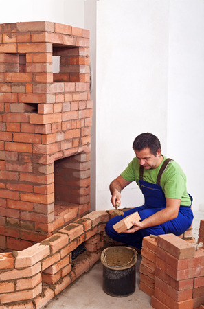 Worker building masonry heater with bricks and clay photo