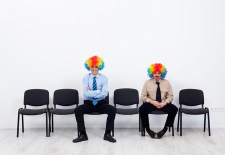 Businessmen wearing clown wigs waiting - sitting on row of chairs photo