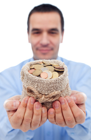 Businessman offering you a bag of euro coins - focus on hands and money photo