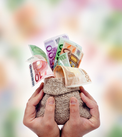 Slave of the money concept - tied up male hands holding bag of euro banknotes photo